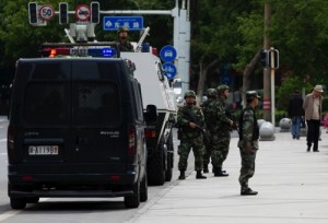 In this May 23 photo, armed Paramilitary policemen stand guard next to their Armored personnel carrier parked near the People's Square in Urumqi
