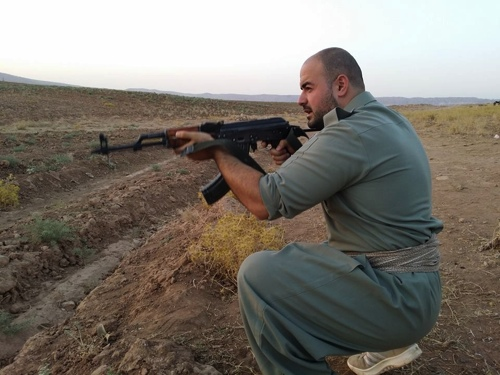 Shaho Pirani shoots with an automantic weapon near the village of Koya in Iraqi Kurdistan in June 2014