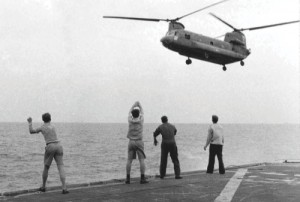 In this April 29, 1975 photo aboard the USS Kirk, crew members signal the Chinook to hover over the deck and drop its passengers out