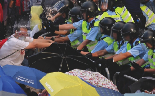Riot police use pepper spray against protesters after thousands of people blocked a main road to the financial central district outside the government headquarters in Hong Kong