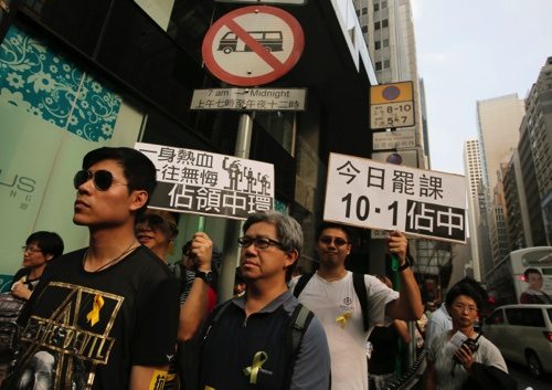 """Protesters raise placards that read """"Occupy Central"""" at the financial Central district during a protest on the third day of a week-long boycott of classes in Hong Kong"""