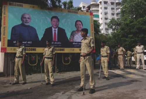 Indian policemen stand next to a welcome board being erected ahead of an anticipated visit by Chinese President Xi Jinping