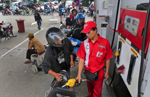 An attendant fills up the tank of a motorbike at a gas station in Jakarta, Indonesia