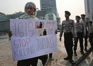 A man holds a poster as police officers stand watch during a rally against the Islamic State group, in Jakarta, on Sept. 5, 2014