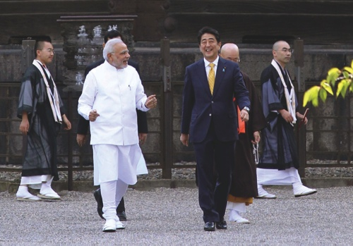 Indian Prime Minister Narendra Modi, front left, and his Japanese counterpart Shinzo Abe, front right, stroll at Toji Temple in Kyoto, western Japan