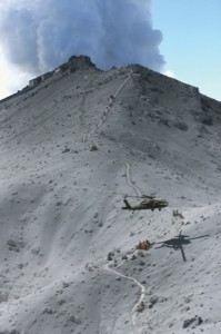 Firefighters and members of Japan's Self-Defense Forces conduct a rescue operation near the peak of Mount Ontake as plumes of smoke billow