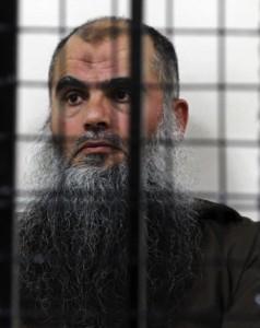The radical al-Qaida-linked preacher Abu Qatada sits behind bars at the Jordanian military court in Amman