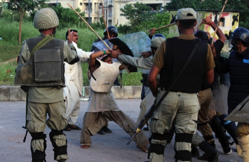 Police beat a protester during clashes in Islamabad, Pakistan
