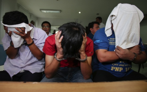 Filipino suspects, from left, Sonny Yohanon, Emmanuel San Pedro and Grandeur Pepito Guerrero, members of a group who call themselves as USAFE, wait for inquest proceedings at the Department of Justice in Manila
