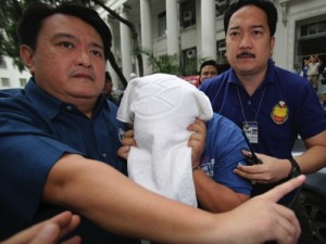 National Bureau of Investigation agents secure alleged USAFE group leader Grandeur Pepito Guerrero, center, who planned to set off firebombs at Manila's international airport and a major shopping mall, as he arrives for inquest proceedings at the Department of Justice in Manila