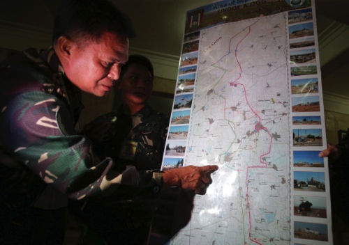 Philippine military chief Gen. Gregorio Pio Catapang shows reporters where Filipino peacekeepers in the Golan Heights have been repositioned during a press conference at Camp Aguinaldo military headquarters in suburban Quezon city, Philippines