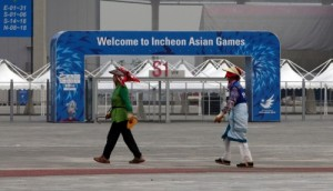 Women walk by the signboard for the 17th Asian Games in Incheon