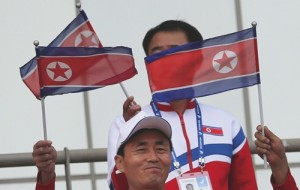 Members of the North Korean delegation cheer their team during the men's first round Group F soccer match between North Korea and Pakistan at the 17th Asian Games
