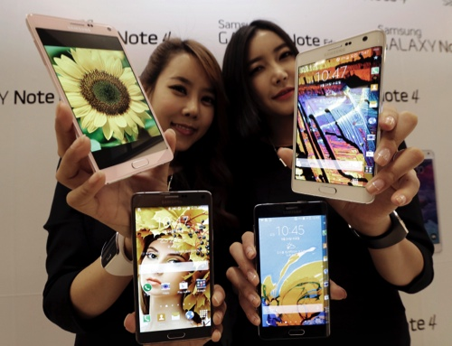 Models pose with Samsung Electronics Co.'s latest Galaxy Note 4 and Galaxy Note Edge smartphones during its unveiling in Seoul