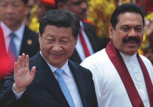 China's President Xi Jinping, left, waves as he walks with Sri Lankan President Mahinda Rajapaksa upon arrival at the airport in Colombo, Sri Lanka