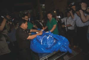 The body of slain British tourist, David Miller, wrapped in a plastic sheet, is carried at a forensic police facility in Bangkok