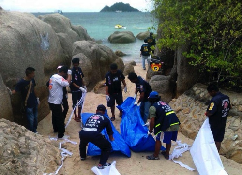 Thai officers work near the bodies of two British tourists