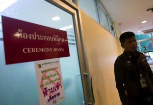 A Thai police officer stands outside a ceremony room as British Embassy officials examine the condition of the bodies of two murdered British tourists inside