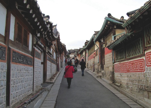 People walking through the historic neighborhood of Buckchon village in Seoul. Buckchon village is one of the few places in Seoul where you can see dozens of traditional Korean houses