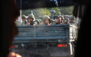 Ukrainian soldiers drive on a truck in the southern coastal town of Mariupol, Ukraine