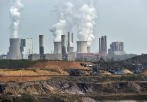 Giant machines dig for brown coal at the open-cast Garzweiler mine in front of a smoking power plant near the city of Grevenbroich in western Germany