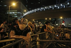 A student protester  is wrapped in plastic to shield from pepper spray