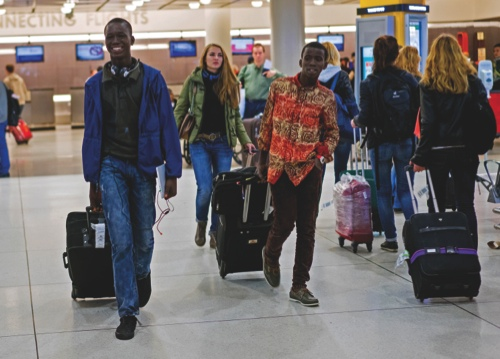 Thomas Nellon, left, 17, and his brother Johnson Nellon, 14, of Liberia, smile at their mother in the arrivals area at John F. Kennedy International Airport in New York
