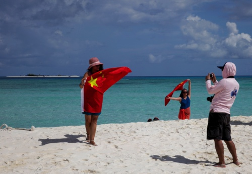 Chinese tourists take souvenir photos with the Chinese national flag as they visit Quanfu island in the Paracels