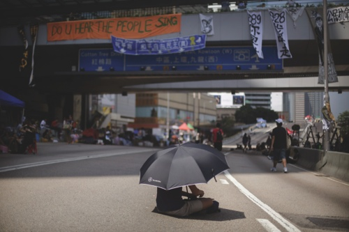A student pro-democracy protester sits alone under the shade of an umbrella on the streets near government headquarters
