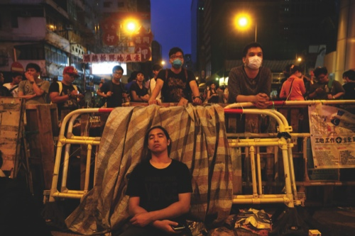 A protester sleeps in front of barricades on a occupied road in Mongkok district