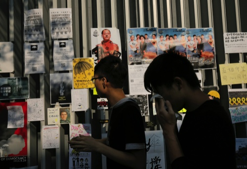 Pro-democracy protesters walk past anti-government posters and papers in the occupied areas surrounding the government complex