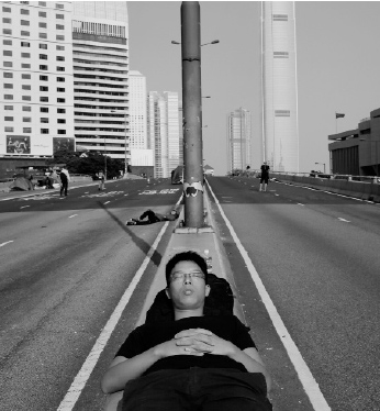 A pro-democracy supporter sleeps on the streets in the occupied areas surrounding the government complex in Hong Kong