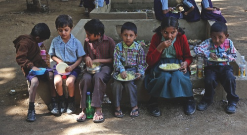 Indian school children sit outdoors and eat lunch at a government school in Hyderabad, India
