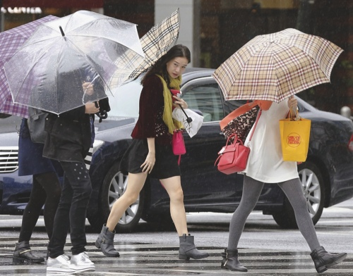 Pedestrians make their way through a street in Tokyo while a powerful typhoon approaches Tokyo
