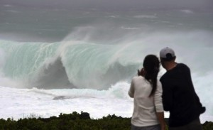 A couple watches huge wave at a cape in Yomitan Village, on Japan's southern island of Okinawa