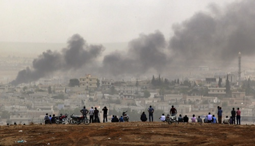 People on a hilltop watch smoke rising from a fire caused by a strike in Kobani, Syria