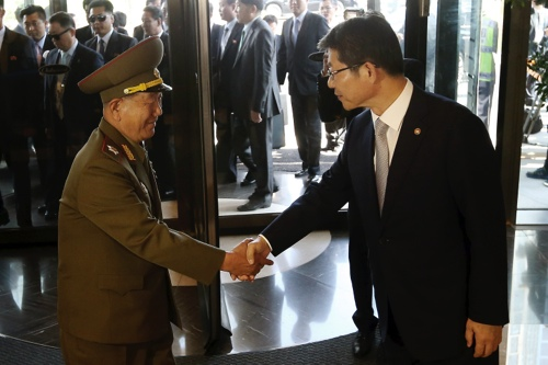 Hwang Pyong So, left, vice chairman of North Korea's National Defense Commission, shakes hands with South Korean Unification Minister Ryoo Kihl-jae upon his arrival at a hotel in Incheon
