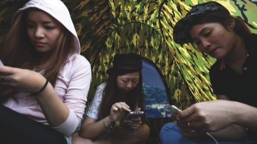 Demonstrators use their mobile devices in their tent outside the Central Government Offices in Hong Kong
