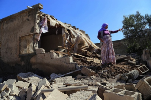 A woman stands in front of her house which is destroyed by a mortar shell, in Alanyurt neighborhood of Sanliurfa's Suruc district, Turkey