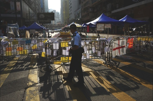 A police officer walks past a barricaded area occupied by demonstrators in the Causeway Bay area of Hong Kong
