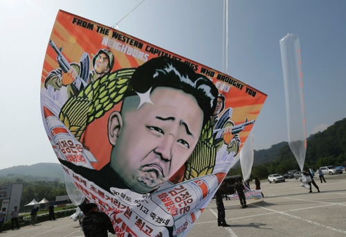 Former North Korean defectors prepare to release balloons carrying leaflets and a banner condemning North Korean leader Kim Jong Un and his government's policies during a rally on the eve of the 66th anniversary of North Korea's founding