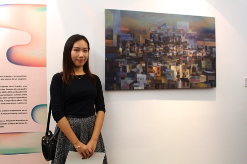 """Lai Sut Weng, 21, poses beside her oil on canvas, """"St Paul's Ruins"""""""