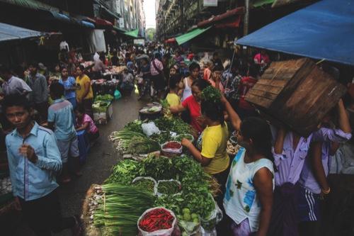 Customers browse vegetables at market stalls in Yangon, Myanmar
