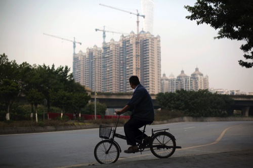 A man on a bicycle rides past cranes operating at a residential construction development in the Haizhu district of Guangzhou