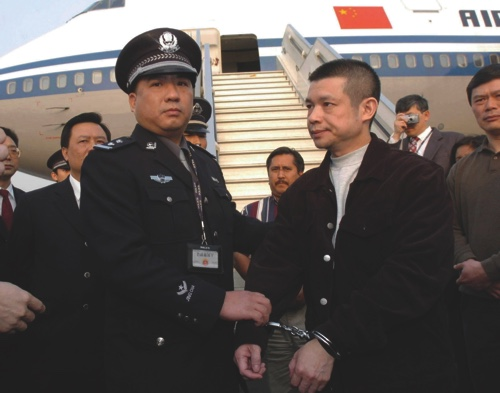 Yu Zhendong, right, accused of embezzling $485 million, is arrested by Chinese police after he was returned by U.S. authorities
