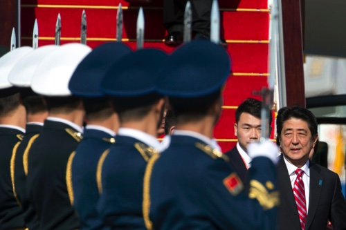 Japanese Prime Minister Shinzo Abe passes by a Chinese guard of honor as he arrives ahead of the APEC Economic Leaders' Week at the airport in Beijing