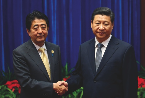Japan's Prime Minister Shinzo Abe, left, and China's President Xi Jinping, right, shake hands during their meeting at the Great Hall of the People, on the sidelines of the APEC summit