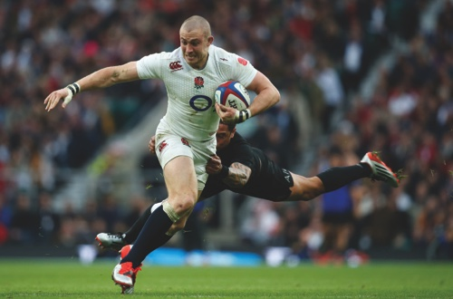 England's Mike Brown runs with the ball as he is challenged by New Zealand's Aaron Smith
