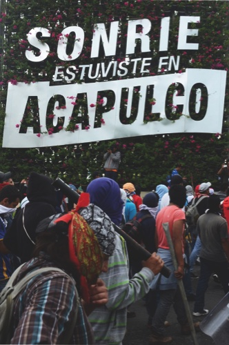 "Masked students block access to the Acapulco airport, where a sign reads in Spanish ""Smile you were in Acapulco,"" as they protest the disappearance of 43 students in the state of Guerrero"