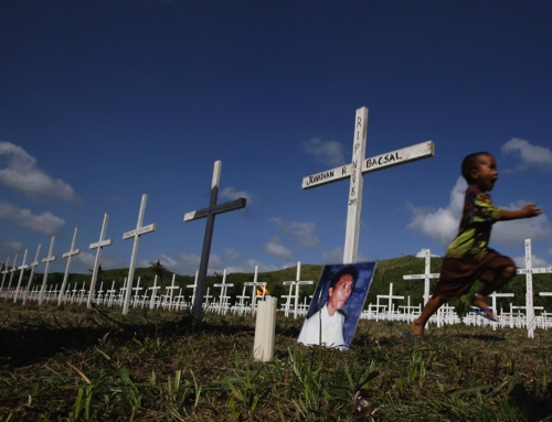Typhoon survivor Jonathan Bacsal Jr. runs past a cross that indicates where his father is buried at a mass grave for typhoon Haiyan victims in the outskirts of Tacloban city, Leyte province